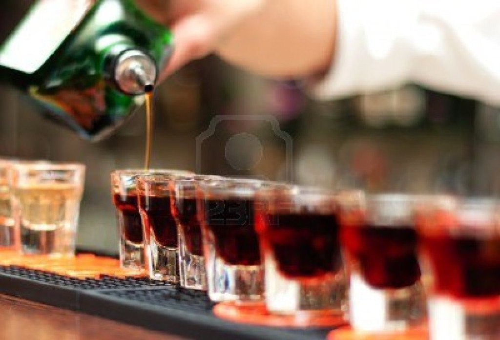 13943533-bartender-pours-alcoholic-drink-into-shot-glasses-on-bar
